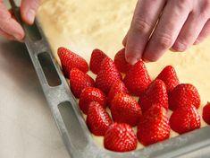 Erdbeeren auf dem Vanillepudding festdrücken