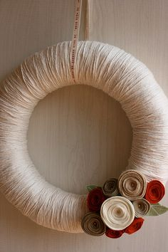 Yarn wrapped wreath with felt flowers. Done this and it isn't hard but takes FOREVER. For next time, get a wreath that is cut so you don't have to loop the yarn through the hole.