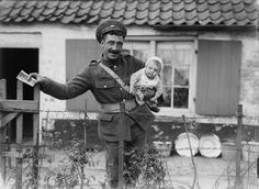 British soldier holding a baby outside a cottage in Adinkerke, 6th August 1917.