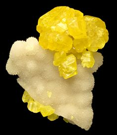 Bright yellow crystals of Native Sulfur perched atop Aragonite. From the Racalmuto Mine, Racalmuto, Agrigento Province, Sicily, Italy.