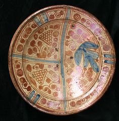 Hispano moresque charger, 17th century, decorated in copper lustre and blue, divided into 3 compartments with stylised grapes and vine leaves, diameter: 34.5cm. 13 1/3in.