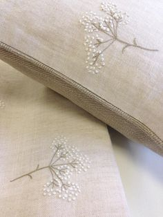 "Piped cushion in Peony and Sage's embroidered Cow Parsley on stone linen, backed with Herringbone ""Cashmere"" linen. By Clarabelle Interiors."