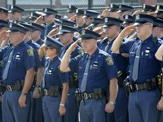 Michigan State Police troopers salute as the casket