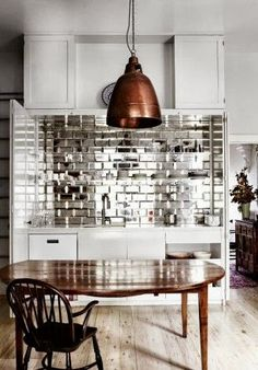 Cool mirror tile splash with big copper pendant and warm wood table below.