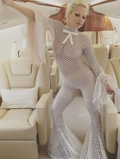 On a private plane, Gaga wears this see-through fishnet jumpsuit boasting flared sleeves and bell bottoms.    - MarieClaire.com