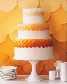 Happy Ombre Cake Twelve shades of orange tones on this white confection give it a warm burst of color, while scalloped embellishments give it a dainty dose of texture and style. Cake by Kate Sullivan/Cake Power Photograph copyright Christina Holmes http://christinaholmesphotography.com/