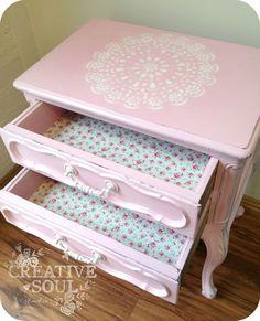 Mesita de noche en rosa con detalles en blanco. Cajones forrados.
