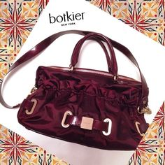 "BOTKIER Satchel w/Dust Bag - Burgundy Wine Authentic Botkier burgundy wine satinlike and patent leather satchel w/ detachable shoulder strap. Measures 15"" X 8"" with double carrying handles measuring 13"" long with a drop of 5"".  Detachable shoulder strap is 27"" long.  Comes with authenticity card and signature dust sleeper bag.  Condition is excellent aside from one small scratch to the gold monogrammed front plate (see last collage).  Gorgeous and very room bag! Botkier Bags Satchels"