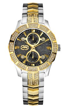 Marc Ecko Midsize E20044M1 Two-Tone Bracelet Watch boasts two metallic tones, highlighted with the help of a deep, black dial and crystal accents. A polished silver-tone stainless steel bracelet band displays crystal-studded accent shapes on ends that join to a stainless steel case. A dazzling, crystal-encrusted gold-tone bezel dramatically frames a richly imprinted black dial that displays polished, gold-tone bar hour indicators as well as an Ecko rhino logo at the nine o'clock. Two gold...