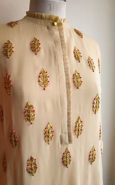 Description: Fine pleated detailing on Collar, placket and sleeves Intricate Gota Patti Handwork Three-quarter sleeves and collared neckline Styling Tip Neck Designs For Suits, Neckline Designs, Dress Neck Designs, Designs For Dresses, Sleeve Designs, Hand Embroidery Dress, Kurti Embroidery Design, Hand Embroidery Designs, Modern Embroidery