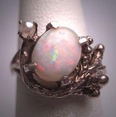 Un maravilloso antiguo Vintage ópalo australiano y anillo de la perla, Retro plata, circa 1950. Este anillo de hermosa finca cuenta con un colorido ópalo australiano mide unos 7 x 9mm. Se trata de un ópalo natural corte genuino, único, no un doblete o triplete. Se une por una perla genuina. El ajuste es un retro plata diseño modernista con detalles imaginativos. General las medidas de anillo alrededor de 7/16 pulgadas de largo por unos 3/4 de pulgada ancho de lado a lado. Tamaño del...
