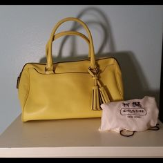 Coach Yellow Legacy Leather Haley Satchel This bag is made of yellow glove-tanned leather with a tan fabric interior. It has a zipper opening at top, with an outer pocket in front. It has 2 open pockets in the interior and a zipper pocket. It has 4 silver metal feet at the bottom. Only flaws are leather wear on the piping at the corners and edges, a small piece worn off on the inside of the handle next to where attached, a small black spot next to zipper and a very small almost unnoticeable…