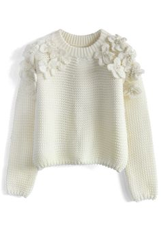 Knit/crochet flowers and add to sweater. Possibly add pearls