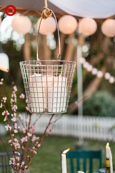 Get your outdoor party glowing with a DIY chandelier and string lights. A candle chandelier is perfect for any backyard space and only requires rope, a basket, and a few large pillar candles. Using the rope, tie the basket to a pergola, tree, or any structure that permits. Then, add in candles and light for a glowing centerpiece. Add in lantern string lights throughout the space to complete the look.