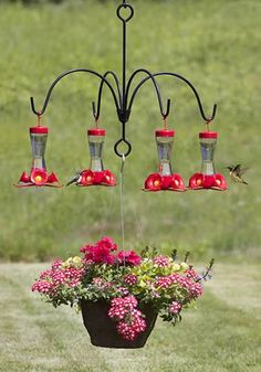 Umbrella Quad Bracket for Hummingbird Feeders... if you can\'t find that, place a 4x4 post in the ground. Secure planter to top of post. Attach four hooks then hang feeders.