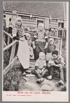 Een groepje kinderen in Marker dracht poseren op het keienpad voor het huis. Over het hek hangen een aantal ankers voor de visserij met staand want. 1893-1910 #NoordHolland #Marken