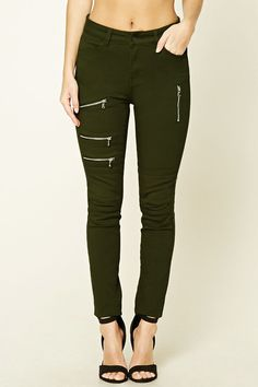 A pair of mid-rise skinny jeans featuring a zippered accents, four-pocket construction, and zip fly.
