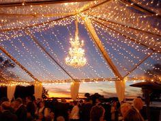 Dreamy outdoor wedding lighting, chandelier and fairy lights. Open air tent, evening wedding reception.