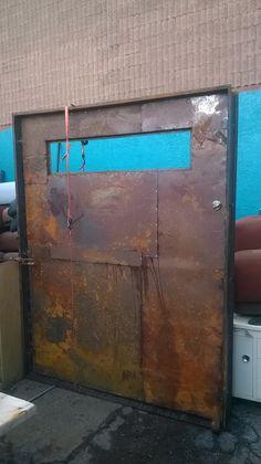 Industrial metal doors.  Center pivot door.  Stands 7' tall by 6' wide.