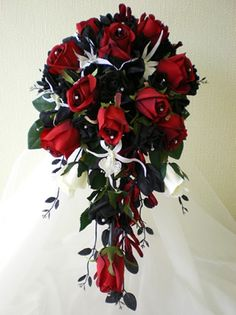 Scarlet  - A medium sized traditional shower bouquet of red, black and ivory  roses with white spider orchids and black lonichera foliage. The roses  in this bouquet have diamante added in the centre. A very striking and  dramatic bouquet for the Bride who wants something a little bit out of  the ordinary.