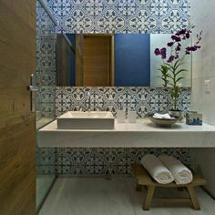 Projeto David Guerra Arquitetura e Interiores. Banheiro com bancada branca e parede com revestimento azul.