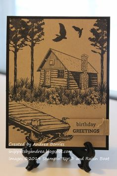 Black card base with a kraft layer featuring a woodsy scene, including trees, dock, log cabin and birds, all stamped in black.