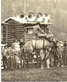 KENNY McLEAN - 1962 RCA World Champion Saddle Bronc Rider competes against 6-time RCA World Champion Casey Tibbs (standing on left with thumbs in his chaps) - Ox Yoke Ranch - Bow Ranch - Nemo, SD - 1963 - Photo by L. E. Henderson.