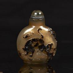 CHINE - XXe siècle  Flacon tabatière en agate grise sculptée en relief sur une face dans la veine brune d'un tigre, chauve-souris et qilong, sur l'autre face de Liu Hai sur son crapaud. Bouchon en verre translucide cerclé de métal.