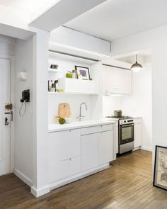 Apartment: Stunning Five to One Apartment Design and Concept in Manhattan by MKCA, White Themed Five to One Kitchen by MKCA with Clean Cabinetry and White Wall Paint Color and Pendant Lamp also Laminate Wood Flooring