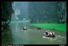 Villagers go to work floating a shallow river in Tam Coc. near Ninh Binh, Vietnam