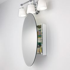Mirrored sides help this wall-hung medicine cabinet almost disappear, putting the emphasis on the oversize oval mirror in front.
