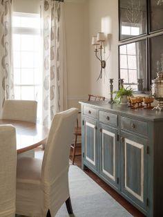 un mueble aparador pintado en un especial tono de azul que combina muy bien con las sillas y paredes blancas.