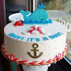 This adorable Whipped Bakeshop nautical baby shower cake comes complete with a cute whale topper and mini crabs! This cake is also decorated with life preservers and rope detailing. Torta Baby Shower, Baby Shower Cakes For Boys, Nautical Baby Shower Cakes, Pirate Baby Shower Ideas, Nautical Cake Pops, Shower Bebe, Baby Shower Fall, Baby Boy Shower, Whale Cakes