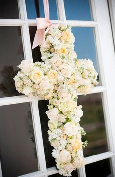 Cross made of flowers. white with hints of light purple. maybe carnations, and babies breath. a little bit of green