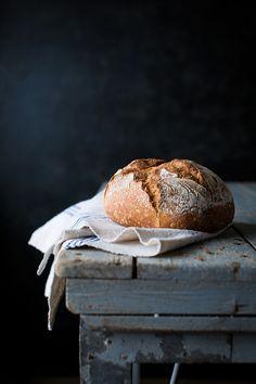 Ein gutes Brot mit einer krossen Kruste, das auf einem schönen Holztisch liegt.