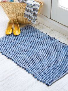 """Strips of material from old jeans create this cushy and practical """"rag-ety"""" rug for any room of the house. It's a great way to use jeans that kids have outgrown. This e-pattern was originally published in the August 2015 issue of Crochet World magazine. Size: 25"""" x 36"""". Made with medium (worsted) weight yarn and size H/8/5mm hook. Skill Level: Easy"""