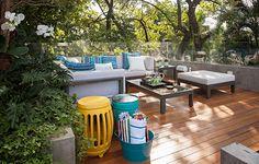 No terceiro andar da casa em São Paulo, o deque de cumaru acomoda os sofás em branco repleto de almofadas, onde o casal recebe os amigos. O espaço é rodeado de árvores graças à ideia da paisagista Bia Abreu, que revestiu as paredes da residência com plantas