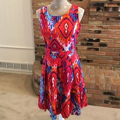 "⭐️HP Badgley Mischka fit & flare Ikat print dress Festive orange/red Ikat/tribal print with shades of turquoise, black, white, Royal blue. 97% cotton, 3% spandex. Lining 200% polyester. Made in China. 15"" across waist. Back zip. 37"" from top of shoulder seam to bottom of hemline. 28"" from armpit across. Great fun dress for many occasions. (HP 5/30/16 Weekend Wardrobe party.) Badgley Mischka Dresses Midi"