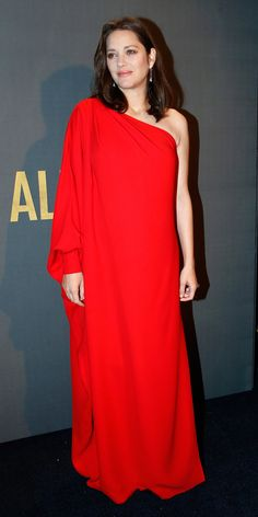 Cotillard dressed her blossoming baby bump in a crimson one-shoulder Dior dress for the Allied premiere in Paris. The radiant free-flowing gown featured a single long sleeve and a modest knee-grazing slit and hinted subtly at the actress's changing silhouette beneath it. from InStyle.com
