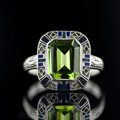 This classic Art Deco ring features a 3.10 carat emerald cut peridot, within a surround of green and blue enamel and a lattice work of 14 karat white gold.
