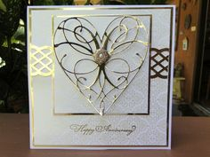 """The card is 5 ½ x5 ½ square    Memory Box La Rue Heart     EkSuccess border punch    Gold mirror Paper    SU Happy Anniversary from """"Something to Celebrate""""    Wedding paper from Jo Ann's    (Squares all just measured and cut with cutter)    Glittered gold embellishment for center of heart"""