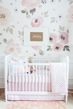A Perfectly Smitten Hello Darling Print, mounted on walls covered in Jolie Wallpaper lined with white wainscoting, is positioned above a white Franklin and Ben Crib accented with Olio Crib Bedding and sat on a Surya Normandy Taupe Area Rug.
