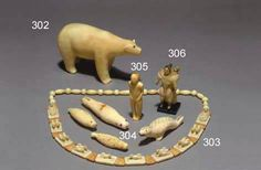 QUATRE AMULETTES INUIT EN IVOIRE  (Alaska)  Chacun représentant un phoque, dont deux tachetés et trois percés pour attachement. Patine crème.