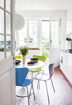 Keittiönlattiassa on haluttu säilyttää vanha kuusikulmainen laatta. Osa valkoisen keittiön kaapeista on alkuperäisiä, osa uusia. Pöydällä suomalaisen Zeenatin neliskulmaisia lautasia.   Onnellisesti vuokralla   Koti ja keittiö   Jutta Ylä-Mononen    Kuva Kirsi-Marja Savola
