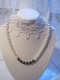 Collana in perle bianche e perle centrali in vetro di colore nero e rondelle argentate con strass. Chiusura collana con moschettone argentato.Lunghezza collana: 44 cm.