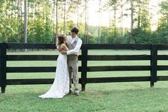 Rustic bride and groom standing by a fence @myweddingdotcom