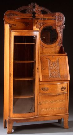 A VICTORIAN OAK CURVED GLASS SECRETARY BOOKCASE WITH CARVED SCROLL DECORATION   c. 1900