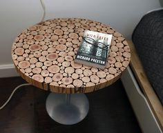 This is a bedside table is made from  branches collected from the owner's property and glued together. The owner used a saw and cut the circular table and sanded it. She bought the silver base off eBay.