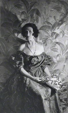 1928 Cecil Beaton photograph, Ottoline in her signature pearls-once belonging to Marie Antoinette, dress taken from the Goya manner of the 18th century style- in a vivid yellow embroidered with mauve and silver flowers