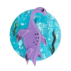 A purple Plesiosaur swimming on a teal background from Erstwilder's newest Erstwildersaurs collection.  Laser cut, hand assembled and hand painted, presented in a branded box as shown, with a cute teapot tag.